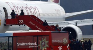 A passenger climbs down an airplane ladder with his hands on his head as police officers stand around hijacked Ethiopian Airlines flight