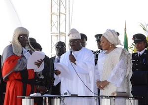Oyo-State-Chief-judge-justice-Munta-Ladapo-Abimbola-administering-oath-of-office-to-Governor-Ajimobi-and-the-wife-Florence-watching-in-admiration