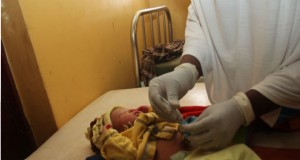 Midwife applying chlorexidine on a newborn