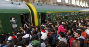 Migrants storm into a train at the Keleti train station in Budapest, Hungary, September 3, 2015 as Hungarian police withdrew from the gates after two days of blocking their entry.
