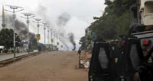 Guinea's security forces are seen as smoke billows