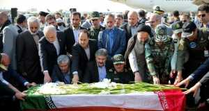 Iranian officials pray as they touch the coffin of a dead Haj pilgrim who was killed in the Sept. 24 Mina crush at Mehrabad airport in Tehran on Saturday. (AP Photo/Ebrahim Noroozi)
