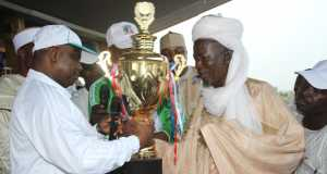 Governor Tambuwal presents a trophy to the representative of Zone One, winners of the state environmental sanitation competition.