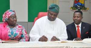 Lagos State Governor, Mr. Akinwunmi Ambode (middle), signing the Y2016 Appropriation Bill into Law, while Deputy Governor, Dr. (Mrs.) Oluranti Adebule (left) and Chairman, Lagos Assembly House Committee on Economic Planning &Budget, Hon. Rotimi Olowo (right), watch keenly, at the Banquet Hall, Lagos House, Ikeja, on Monday