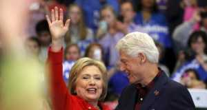 U.S. Democratic presidential candidate Hillary Clinton (L) waves after being introduced onto the stage by husband, former U.S. President Bill Clinton, during a campaign rally at Washington High School in Cedar Rapids, Iowa January 30, 2016.