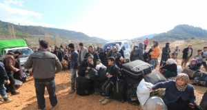Internally displaced Syrians fleeing advancing pro-government Syrian forces wait near the Syrian-Turkish border after they were given permission by the Turkish authorities to enter Turkey,