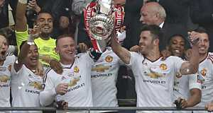 Manchester United's English striker Wayne Rooney (centre left) and Manchester United's English midfielder Michael Carrick lift the trophy as players celebrate their victory after extra time in the English FA Cup final football match between Crystal Palace and Manchester United at Wembley stadium in London on May 21, 2016. Manchester United won the game 2-1, after extra time.