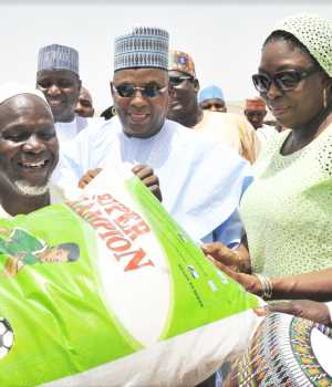 M.D. Dangote Foundation, Zouera Youssoufou, (Right) Presenting Food Items to one of The Beneficiary with A Bag of Rice (Left) While Borno State Governor (Middle) Alhaji Kashim Shettima, At The Distribution of Dangote Foundation Donate Foods Items for Ramadan to (IDP) Internal Displays People of Bakkasi Camp in Maiduguri Borno State
