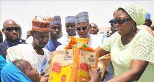M.D. Dangote Foundation, Zouera Youssoufou, (Right) Presenting Food Items to one of The Beneficiary with his Father (Left) While Borno State Governor (Middle) Alhaji Kashim Shettima, At The Distribution of Dangote Foundation Donate Foods Items for Ramadan to (IDP) Internal Displays People of Bakkasi Camp in Maiduguri Borno State