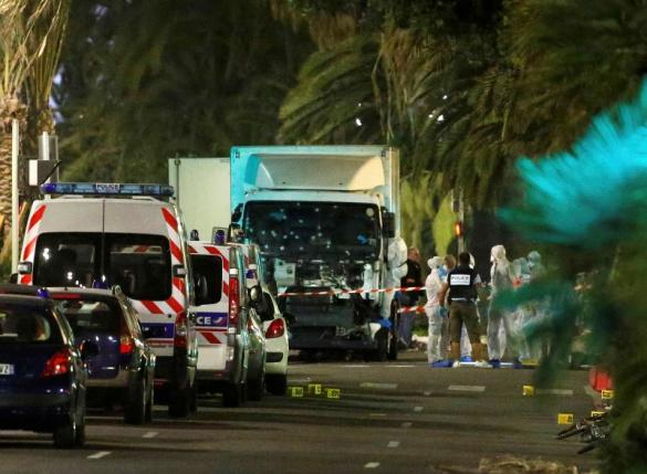 French police forces and forensic officers stand next to a truck July 15