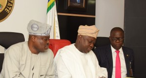 Lagos State Governor, Mr. Akinwunmi Ambode (middle), signing the Property Protection and Neighbourhood Safety Agency Laws flanked by the Speaker, Lagos House of Assembly, Rt. Hon. Mudashiru Obasa and Attorney General & Commissioner for Justice, Mr. Adeniji Kazeem at the Conference Room, Lagos House, Ikeja, on Monday