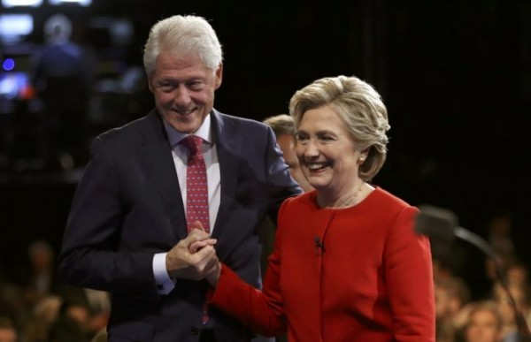 Hillary Clinton holds hands with her husband, former President Bill Clinton, as they leave the stage.