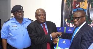Lagos AG Kazeem Adeniji(r) hands over documents to DCP Bolaji Salami