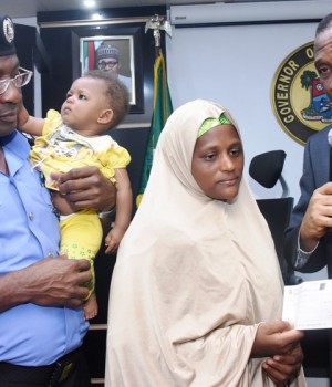 Lagos SSG Tunji Bello, presenting a cheque to widow of one of the killed Policemen in Ishawo, Ikorodu, Mariam Mamuda, while the Commissioner of Police, Fatai Owoseni, carries her baby, Aishat during the presentation