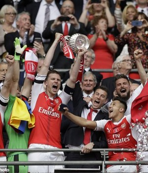 Arsenal's players celebrate with the trophy after winning the English FA Cup final soccer match between Arsenal and Chelsea at the Wembley stadium in London, Saturday