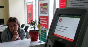 An employee sits next to a payment terminal out of order at a branch of Ukraine's state-owned bank Oschadbank after Ukrainian institutions were hit by a wave of cyber attacks earlier in the day, in Kiev