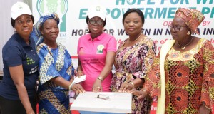 Mrs. Ambode presenting empowerment items to a widow
