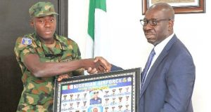 David Iboi, one of the newly graduated soldiers of Edo State indigene from the Nigerian Air Force, Airmen Training School, Kaduna presenting an almanac of the NAF '17A Set to Governor Godwin Obaseki