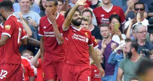Liverpool's Egyptian midfielder Mohamed Salah (R) celebrates with teammates after scoring their third goal during the English Premier League