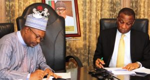 Tunji Bello (right) and Permanent Secretary, State House Abuja, Mr. Jalal Arabi (left), signing documents during the official hand-over of the Presidential Lodge, Marina