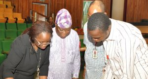 GM, Supply Chain Management, Mrs. Sophia Mbakwe (first Left), examining bid documents with some representatives of companies at the bid opening exercise for firms to provide security services at the NNPC's depots and pump stations