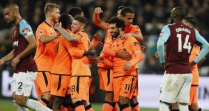 Liverpool's Mohamed Salah celebrates with teammates after defeating West Ham