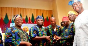 Gov. Ambode presenting jey of a bus to best CDA during the Community Development Day