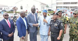 Tunji Bello, representing Gov. Ambode presents keys to the bikes to Lagos Police boss Imohimi Edgal