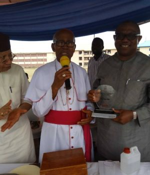 The Catholic Archbishop of Owerri, Most Rv. Dr. Anthony Obinna (Middle), presenting the 2018 Award for Outstanding Contribution to Excellence in Education to Peter Obi (right) at the Assumpta Cathedral Field, Owerri, on Monday, while Dr. Paschal Dozie (Left) watches with excitement.
