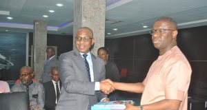 Peterside presenting a copy of the Nigeria's maritime industry forecast to the Director General of the Bureau of Public Enterprises (BPE), Alex Okoh when he paid a courtesy visit to the head office of NIMASA in Lagos