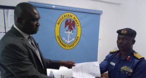 EFCC official, Richard Ogberagha, receiving the hand over note from Captain Adeyemi F. Adewuyi
