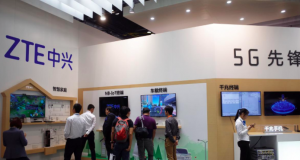 Visitors are seen at a booth of Chinese telecom equipment maker ZTE Corp at an expo in Beijing,