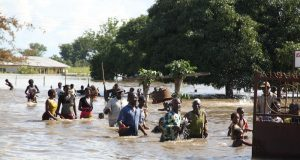 People wading through the flood water