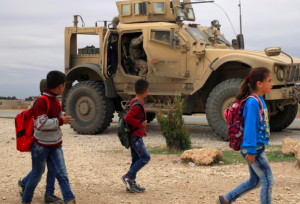 Syrian schoolchildren walk as U.S. troops patrol near Turkish border in Hasakah, Syria Nov. 4, 2018.