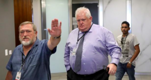 A member of the security gestures to the photographer as former Bosasa Chief Operations Officer, Angelo Agrizzi arrives at the Judicial Commission of Inquiry