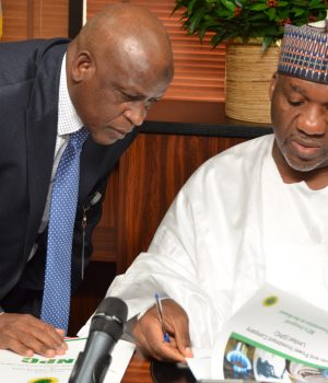 Isiaka Abdulrazaq (right), being shown some documents by MD, Gas and Power Investment Company (GPIC), Mallam Hussaini El-Yakubu,