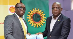 Bayo Ojulari (right) presenting a copy of SNEPCo's In Pursuit of Excellence, to the Nigeria Council Chair, Society of Petroleum Engineer, Debo Fagbami,