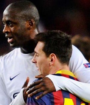 Yaya Toure cuddles Barcelona's Messi