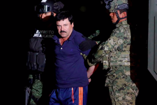 "oaquin ""El Chapo"" Guzman is escorted by soldiers during a presentation in Mexico City"