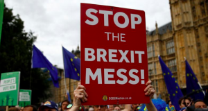 An anti-Brexit protestor holds a placard outside the Houses of the Parliament in London