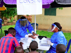 Ugandan health workers speak to civilians before carrying out the first vaccination exercise against the ebola virus