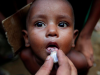 : A Rohingya refugee child gets an oral cholera vaccine, distributed by the World Health Organisation