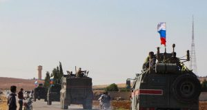 A convoy of Russian military vehicles drives toward the northeastern Syrian city of Kobane