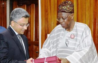 Lai Mohammed (right), presenting a souvenir to the Indian High Commissioner to Nigeria, Abhay Thakur
