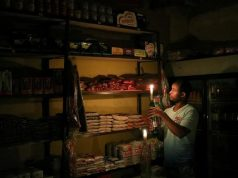 "An owner of a convenience store, or ""spaza shop"", picks an item for a customer as he holds a candle, in Senaone, Soweto, South Africa"