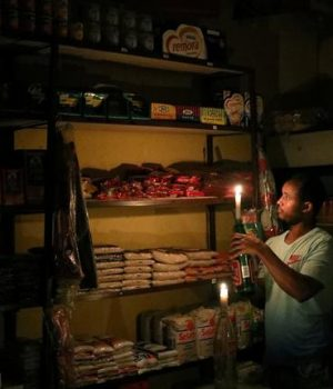 """An owner of a convenience store, or """"spaza shop"""", picks an item for a customer as he holds a candle, in Senaone, Soweto, South Africa"""