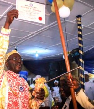 Akinadewo displaying the certificate of investiture