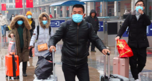 Mask wearing passengers at a train station