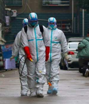 Workers from local disease control and prevention department in protective suits disinfect a residential area