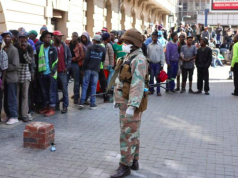A member of the South African National Defense Forces keeps watch as homeless men stand in a queue during the first day of a nationwide lockdown